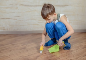 Child using toy broom and dustpan
